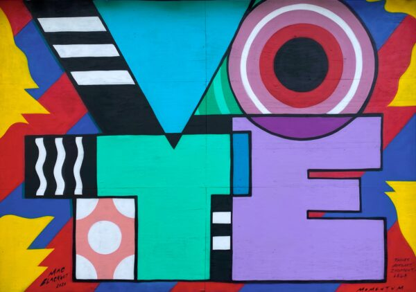 Graffitti on a wall saying 'vote'