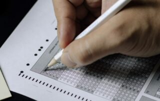 image of a hand holding a pencil and checking answers on a test